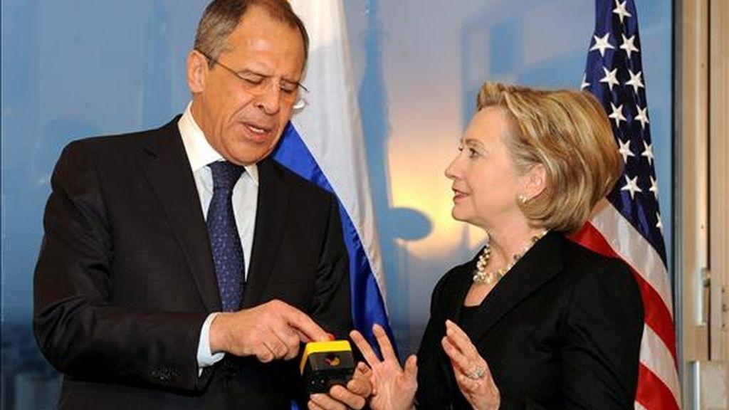 La secretaria de Estado estadounidense, Hillary Clinton (d), y el ministro de Asuntos Exteriores ruso, Sergey Lavrov, charlan después de que Clinton hiciera entrega a Lavrov de un artefacto con un botón rojo durante la reunión que mantuvieron en el hotel Continental de Ginebra (Suiza), el pasado 6 de marzo. EFE/Archivo