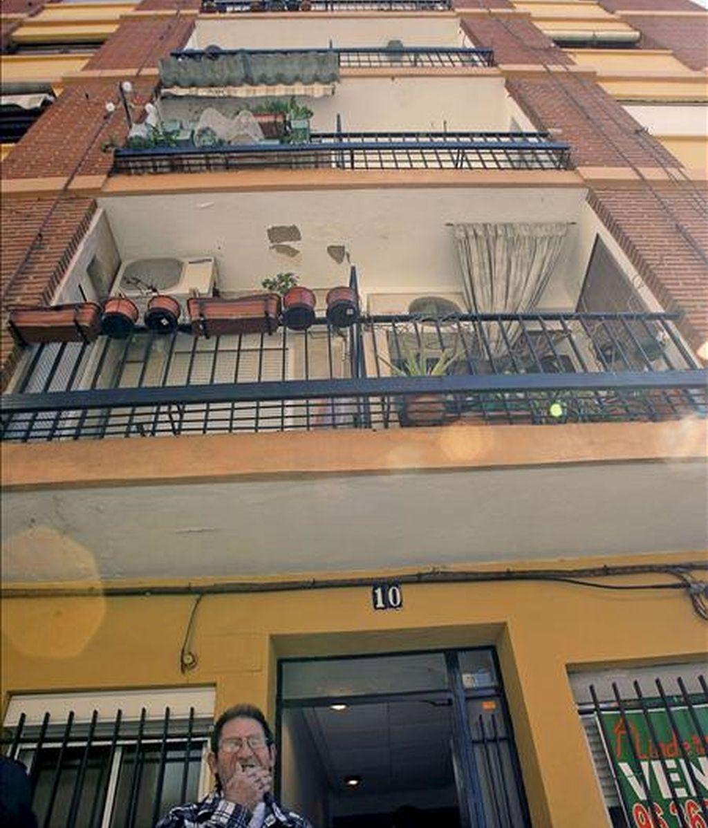 Un vecino permanece en el exterior del inmueble de Burjassot (Valencia), donde un hombre de 58 años ha asfixiado a su hermana, de 57, y después se ha suicidado. EFE