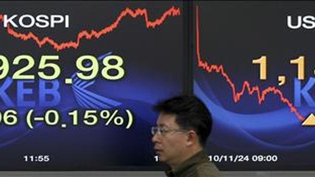 Un agente de bolsa pasa junto a un panel que muestra el valor alcanzado por el índice Kospi del mercado surcoreano en Seúl. EFE