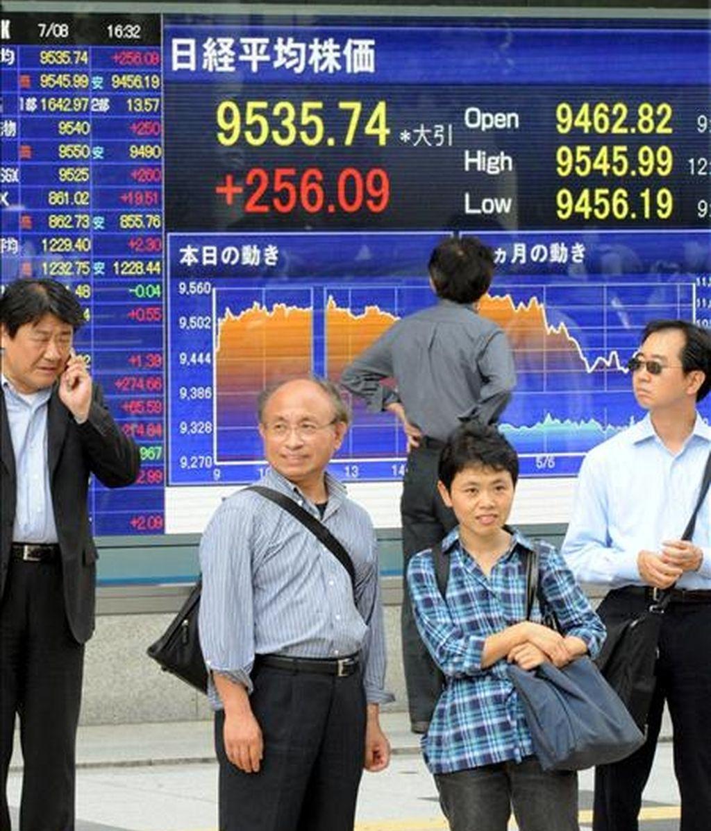 Varios japoneses pasan ante una pantalla en la que aparece el índice Nikkei, en el centro de Tokio (Japón). EFE/Archivo