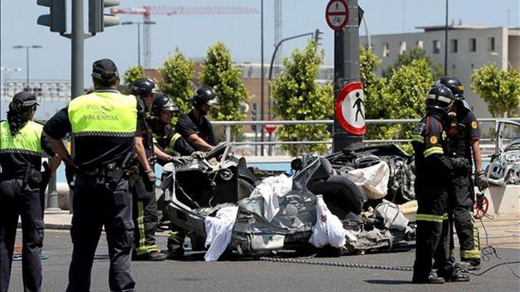 Varios bomberos mueven los restos del turismo en el que viajaban dos jóvenes y que, tras saltarse un semáforo en rojo, fue arrollado por un tranvía esta mañana en la avenida de Cataluña de Valencia. EFE