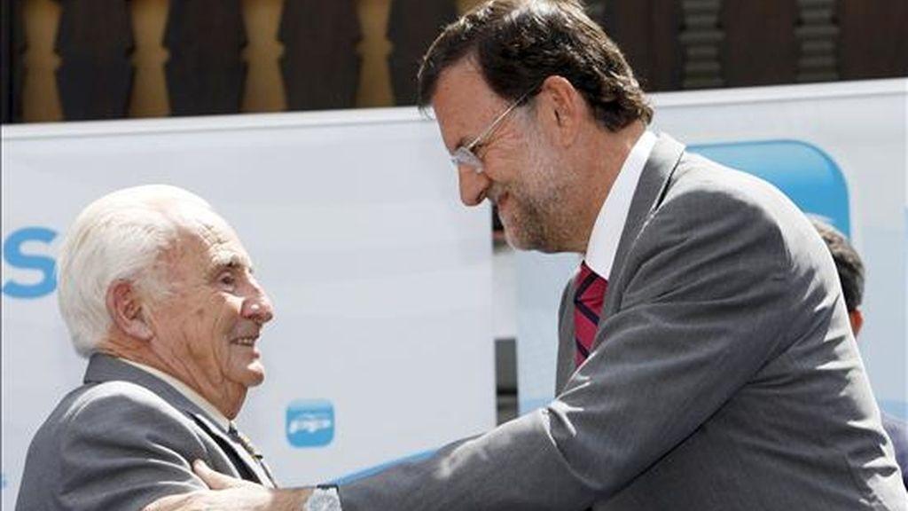 El presidente del PP, Mariano Rajoy (d), saluda al alcalde de la localidad abulense de Cuevas del Valle, Licinio Prieto (i), durante el homenaje que ha recibido por ser, a sus 87 años, el alcalde más viejo de España. EFE
