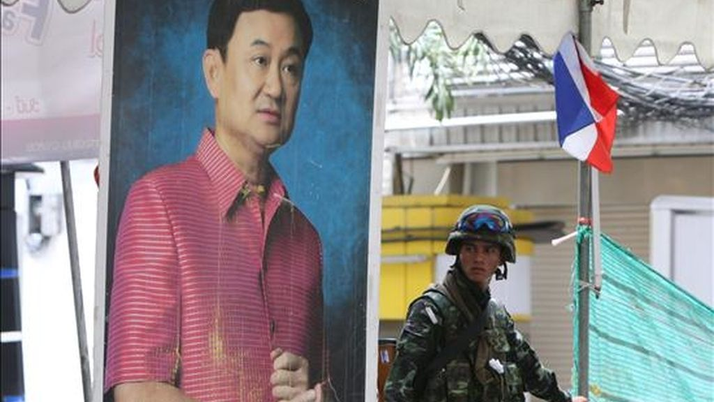 """Un soldado es fotografiado junto a una imagen del ex primer ministro tailandés Thaksin Shinawatra donde se lee """"por favor confiar en el sistema parlamentario"""" en el centro de Bangkok (Tailandia), el pasado 20 de mayo. EFE/Archivo"""
