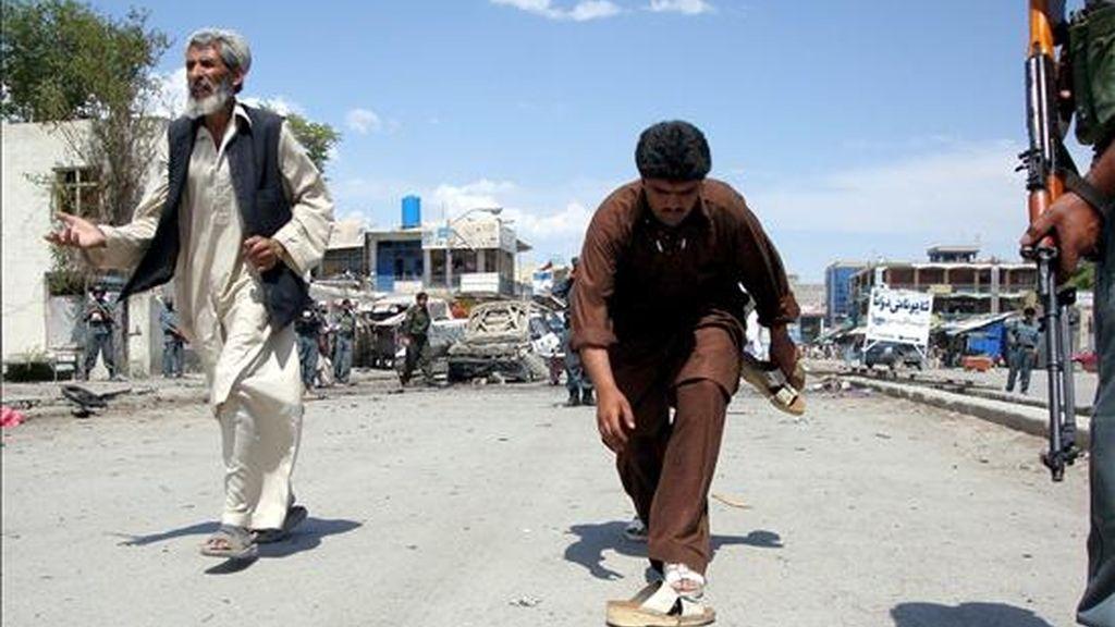 Un oficial de las fuerzas de seguridad afgano inspecciona el lugar en el que ayer, 22 de junio, se registró un doble atentado suicida. EFE