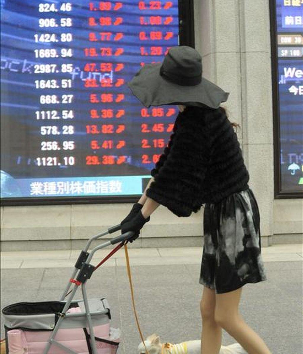 Una mujer camina frente a un tablero electrónico con los ínidices de la bolsa de Tokio. EFE/Archivo