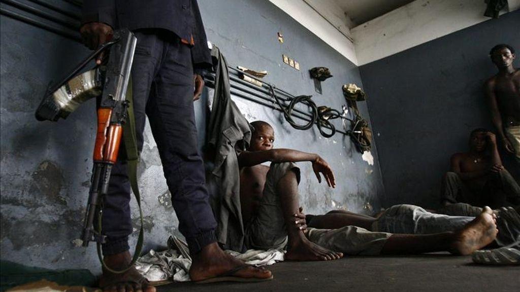 Un soldado fiel al presidente Alassane Ouattara vigila prisioneros leales al expresidente Laurent Gbagbo en Yopougon, Abiyán, Costa de Marfil. EFE