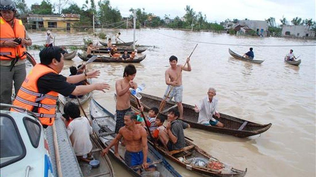 Un grupo de personas utiliza botes para acercarse a los trabajadores municipales que realizan labores de rescate, tras una tormenta tropical en Vietnam. EFE/Archivo