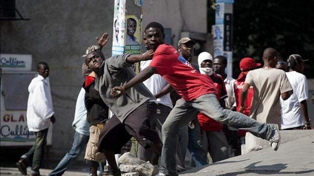 Dos jóvenes arrojan piedras contra un grupo de cascos azules de MINUSTAH que custodian los alrededores del Consejo Electoral Provisional (CEP) en el suburbio de Petion Ville, en Puerto Príncipe (Hiatí). EFE