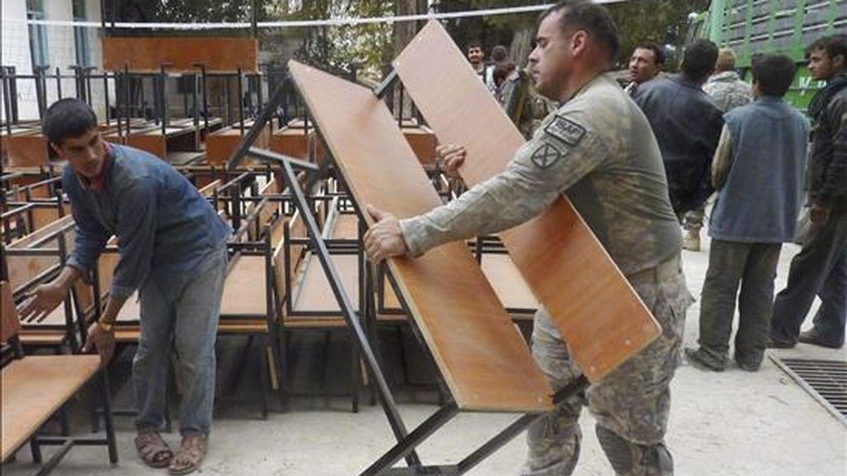Un soldado estadounidense de la ISAF (Fuerza de Asistencia y Seguridad Internacional), ayuda a descargar mobiliario escolar de un camión en la ciudad de Kunduz, Afganistán. EFE/Archivo