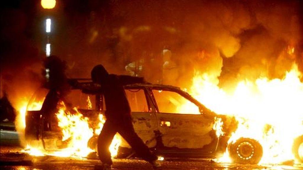 Un protestante nacionalista lanza objetos a la policía en la zona Ardoyne, norte de Belfast, Irlanda del Norte, la noche del 12 de julio. EFE