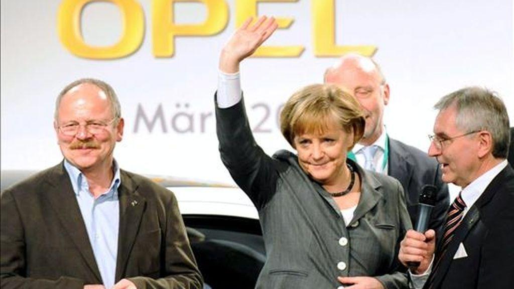 El presidente del comité de empresa de Opel, Klaus Franz; la canciller alemana, Angela Merkel; y el presidente de Adam Opel Ldt., Hans Demand, saludan tras el discurso pronunciado ante los cerca de 3 mil empleados de la planta Opel en Ruesselsheim, Alemania, hoy martes 31 de marzo. Merkel realizó una visita a la planta con el objetivo de discutir el futuro del fabricante alemán. EFE