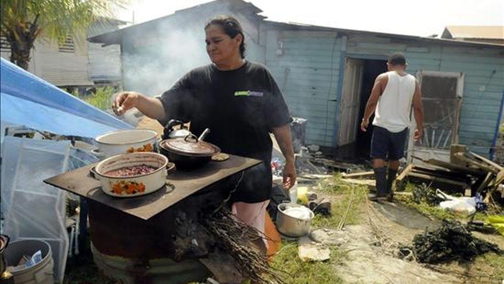 Una mujer prepara la comida fuera de su casa, afectada por el terremoto que hace una semana sacudió el norte de Honduras. EFE/Archivo