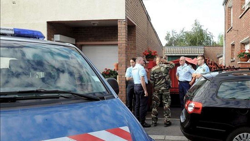 Miembros de la Gendarmería francesa esperan de pie delante de una casa en Villers-au-Tertre, cerca de Lille, al norte de Francia. EFE