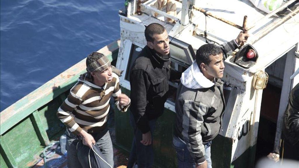 Migrantes norafricanos miran desde uno de los dos botes rescatados por la Guardia Costera en la costa de Lampedusa, Italia. EFE