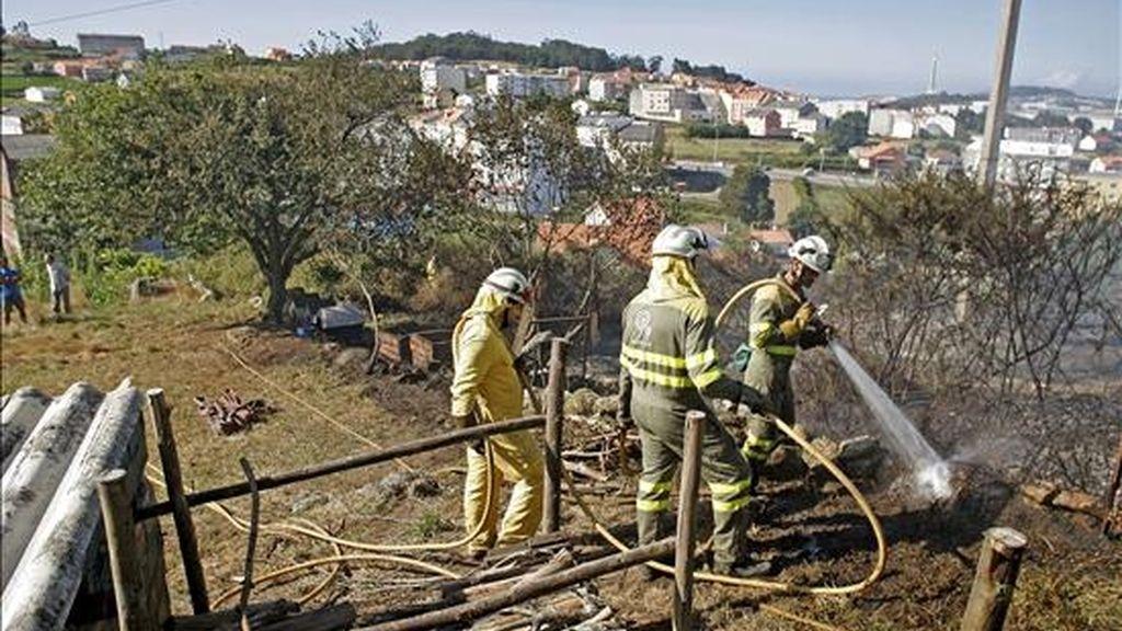 Varios bomberos refrescan una zona afectada por el reciente incendio forestal en Santiago de Artexio, en A Coruña. En otro incendio en esta provincia ha sido hallado hoy el cadáver de una mujer. EFE/Archivo