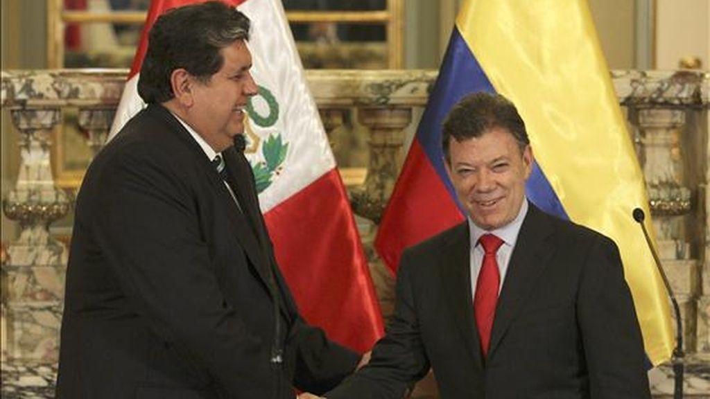 El presidente electo de Colombia, Juan Manuel Santos (d), estrecha la mano del mandatario peruano, Alan García (i), el pasado 27 de julio de 2010, durante una reunión en el Palacio de Gobierno en Lima (Perú). EFE/Archivo