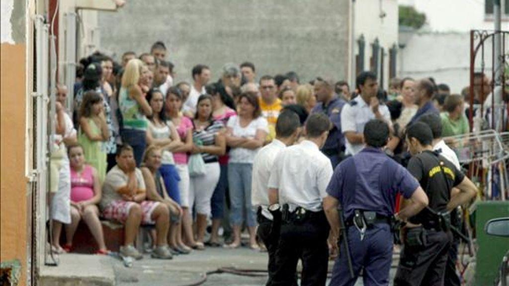 Varios miembros de la Policía junto al cadáver de una mujer que ha fallecido en un incendio registrado hoy en una vivienda de La Línea de la Concepción (Cádiz), en el que otras dos personas han resultado heridas, una de ellas una niña. EFE