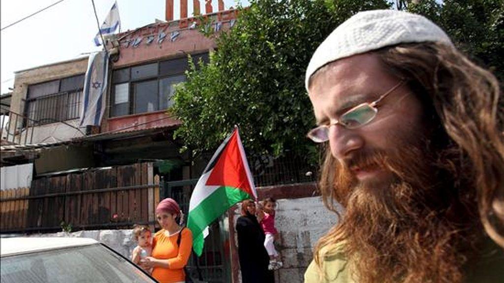 Una familia de colonos judíos saliendo este lunes de su casa en Sheij Yarraj, en la zona árabe de Jerusalén, mientras la familia Al Ghawi espera junto a la puerta del que fue su hogar con una bandera palestina. EFE