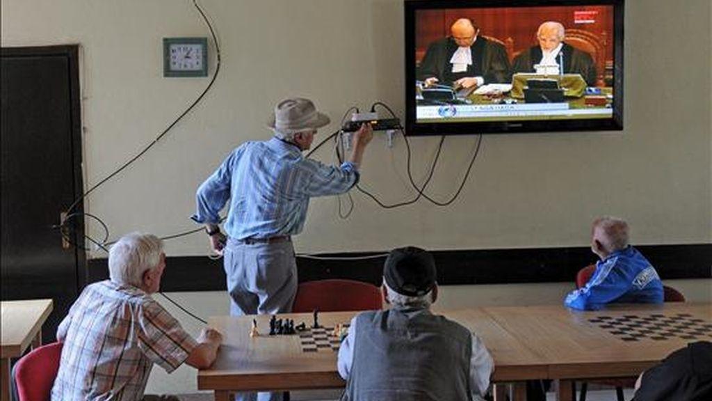 Albano kosovares siguiendo por televisión la lectura del dictamen del tribunal de La Haya sobre la legalidad de la declaración de independencia de Kosovo, este jueves en Pristina. EFE