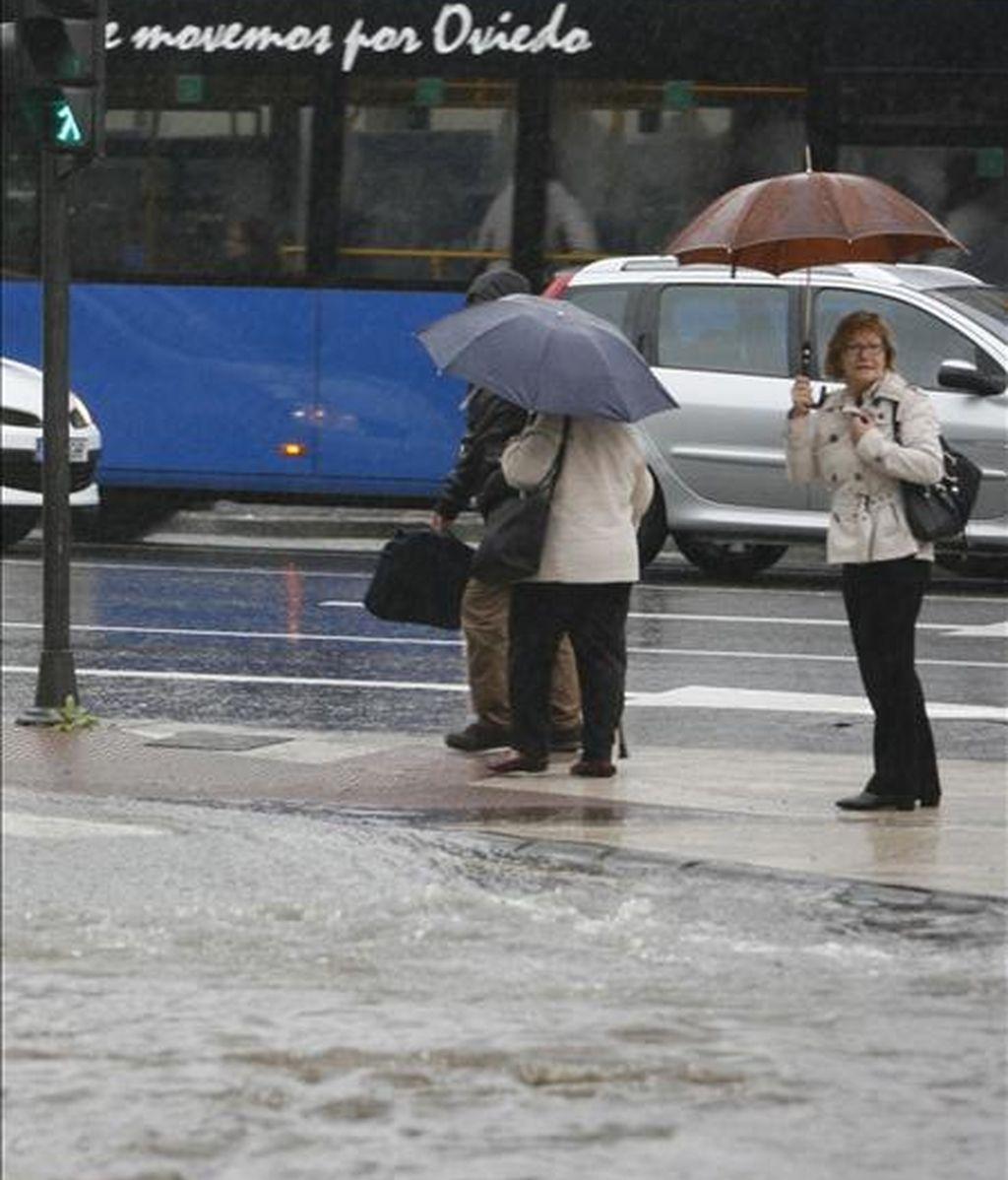 Varias personas se protejen de la lluvia con su paraguas. EFE/Archivo