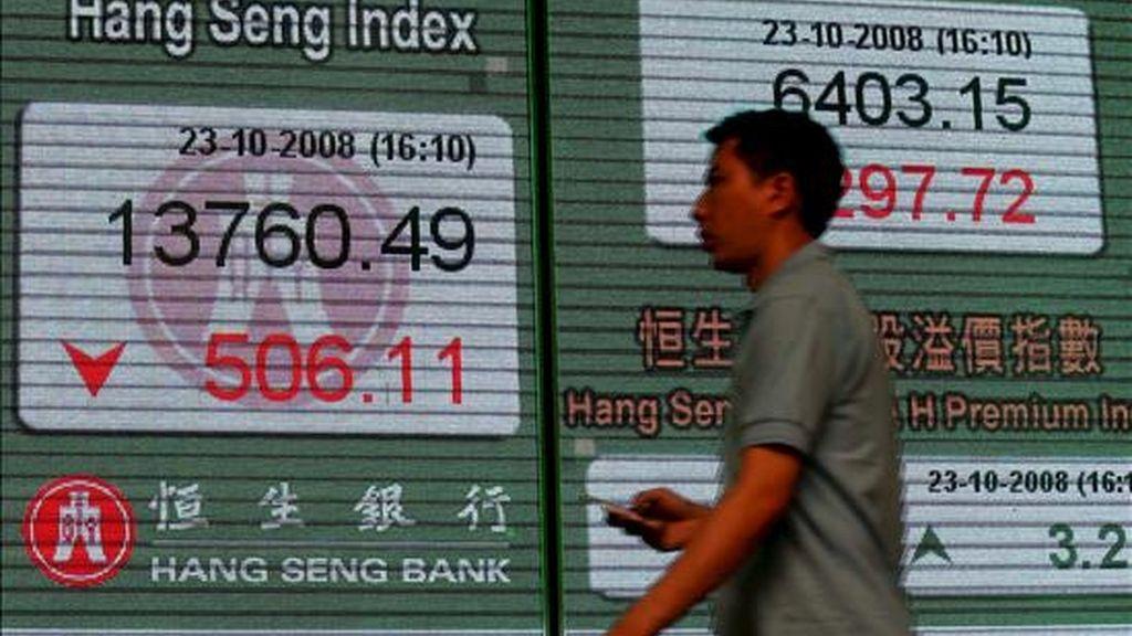 Un viandante pasa por delante de un panel electrónico con información del Índice Hang Seng en un banco de Hong Hong. EFE/Archivo
