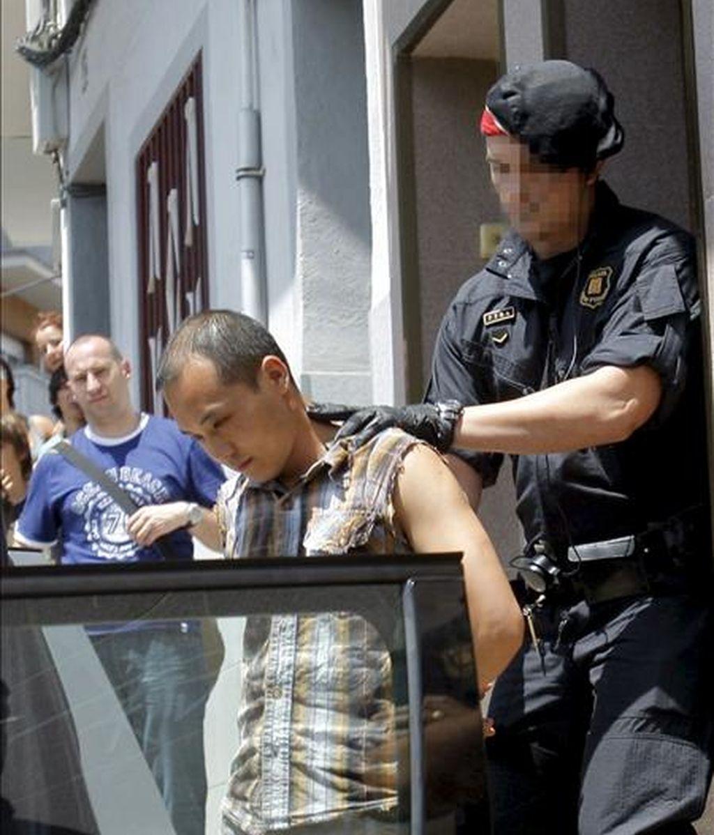 Un agente de los Mossos d'Esquadra traslada a uno de los detenidos durante la operación en la que se han registrado unos 70 talleres clandestinos textiles regentados por ciudadanos de origen chino en Mataró (Barcelona). EFE/Archivo