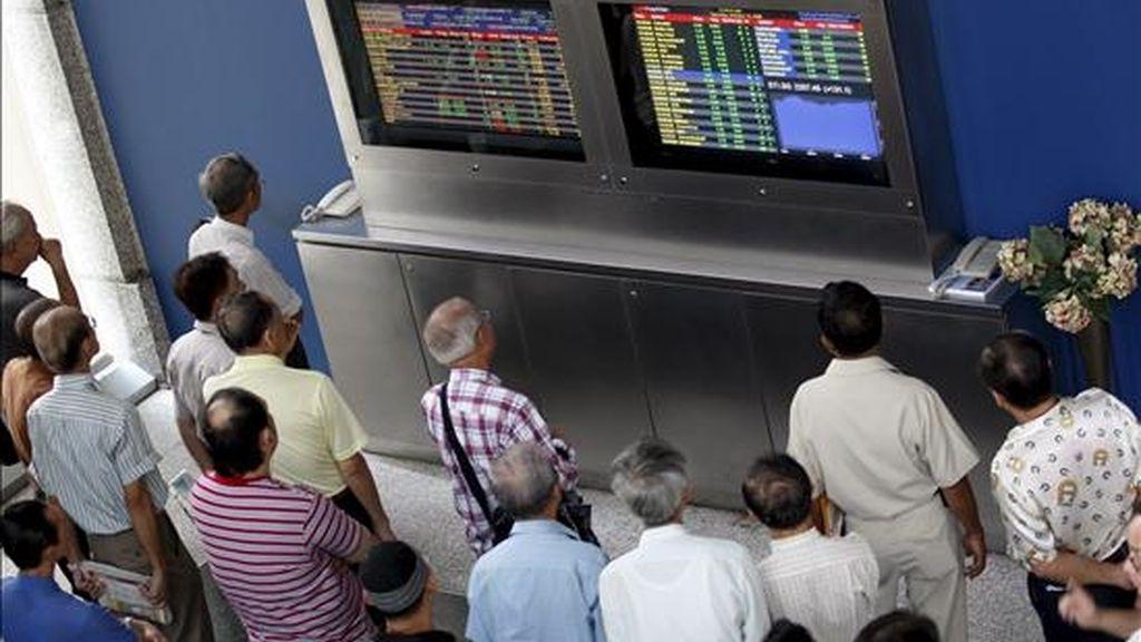 Un grupo de inversores observa unos monitores en los que se muestran los valores de la Bolsa de Singapur. EFE/Archivo