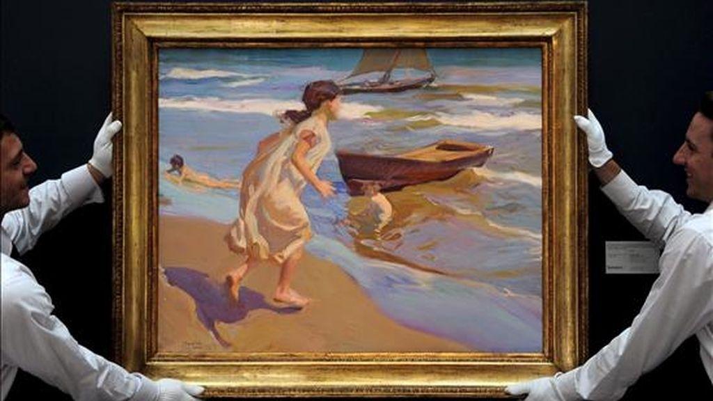"""En la imagen de archivo, unos empleados de la casa de susbastas Sotheby's cuelgan el cuadro """"Niña entrando en el baño"""", del pintor español Joaquín Sorolla, fechado en 1917. EFE"""