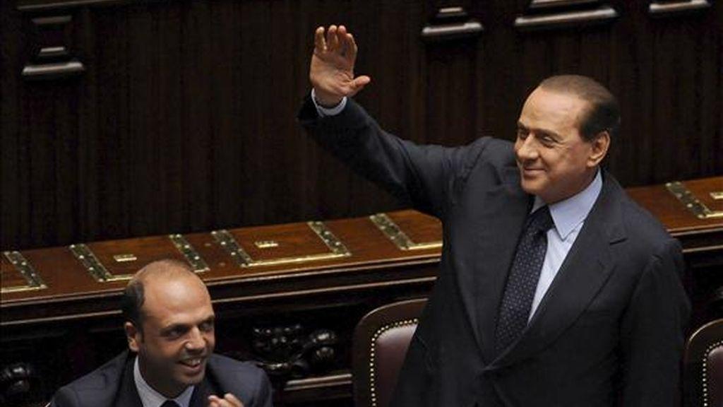 El primer ministro italiano Silvio Berlusconi (i), junto al ministro italiano de Justicia, Angelino Alfano, (i), saluda a sus diputados tras salvar con una mayoría simple la moción de censura presentada por la oposición contra el subsecretario de Justicia, Giacomo Caliendo, en el parlamento en Roma, (Italia). EFE