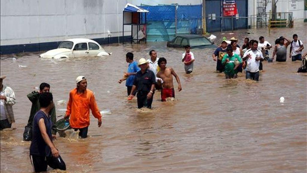 """El paso del huracán """"Karl"""" por el estado mexicano de Veracruz dejó un millón de personas damnificadas, 150.000 evacuados, doce muertos y daños por unos 50.000 millones de pesos (3.900 millones de dólares), afirmó hoy el gobernador de esa región del Golfo de México, Fidel Herrera. En la imagen, varias personas caminan por una calle de la ciudad mexicana de Veracruz, afectada por las recientes inundaciones provocadas por las lluvias del huracán """"Karl"""". EFE"""