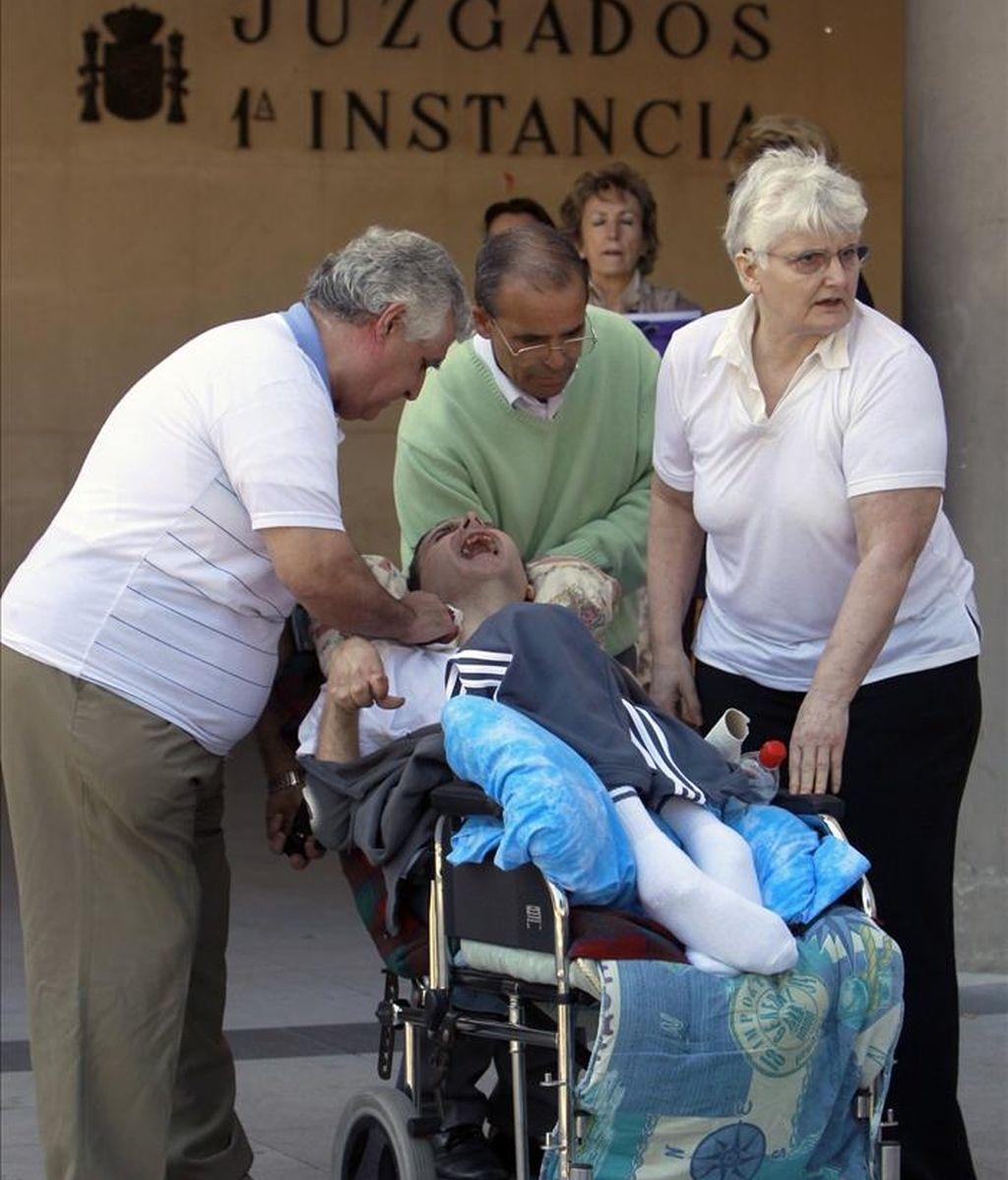 Antonio Meño (en la silla), el hombre que ha permanecido más de 21 años en coma tras ser sometido a una intervención quirúrgica, y sus padres, Antonio (i) y Juana Ortega (d), a la salida hoy del Juzgado de Instrucción número 15 de Madrid. EFE