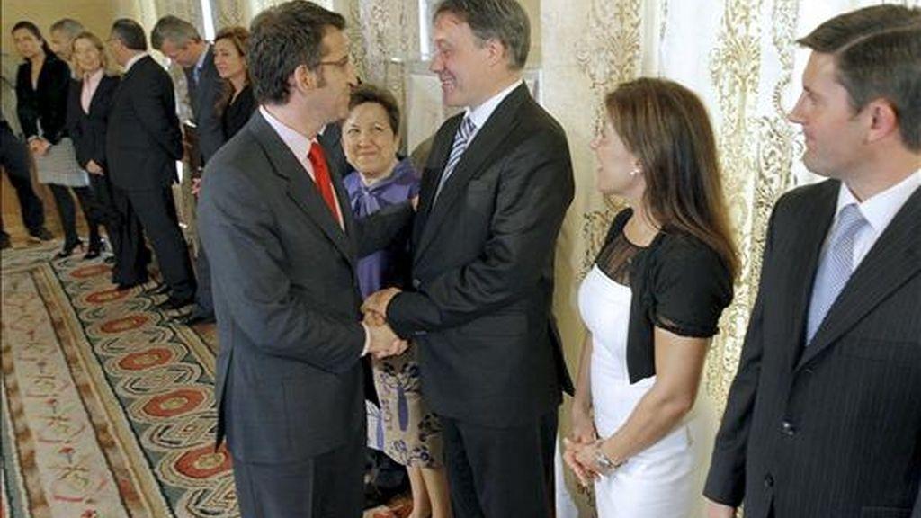 El presidente de la Xunta, Alberto Núñez Feijóo (i), saluda a su equipo de conselleiros, tras tomar éstos posesión del cargo, esta mañana en el Palacio de Raxoi, en Santiago de Compostela. EFE