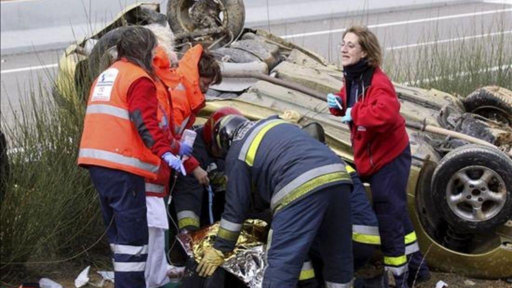 Integrantes del cuerpo de Bomberos y de los servicios de Emergencia atienden a la mujer de 52 años que ha resultado herida grave al salirse de la vía un turismo y dar varias vueltas de campaña en la A-67 (Cantabria-Meseta), a la altura del término palentino de Fuentes de Valdepero. EFE