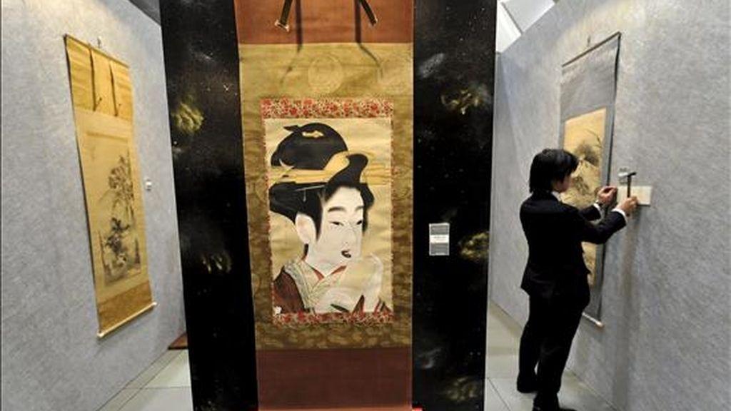 Un empleado coloca una placa junto a una obra del artista japonés Gion Seitoku durante la Feria de Arte de Tokio (Japón), hoy, 2 de abril. Cerca de 150 galerías presentan durante tres días las obras de unos 650 artistas.EFE/Franck Robichon