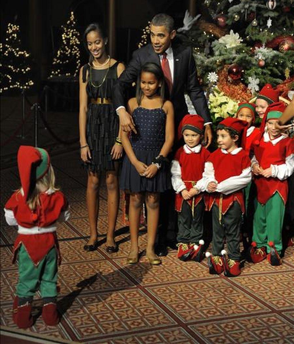 El presidente Obama, y sus hijas Malia (i) y Sasha (2i), posan junto a un grupo de niños, durante la celebración de la fiesta navideña en el Museo Building de la ciudad de Washington D.C (EEUU). EFE