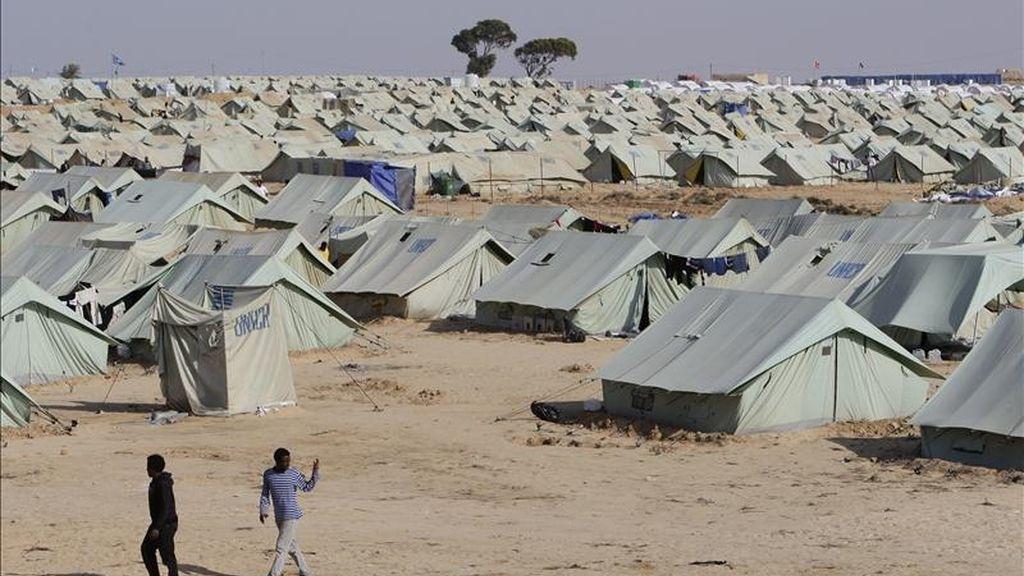 Dos hombres caminan cerca a las tiendas del campo de refugiados Bouchoucha ubicado a algunos kilómetros de la frontera con Libia, en Ras Jedir (Túnez). EFE