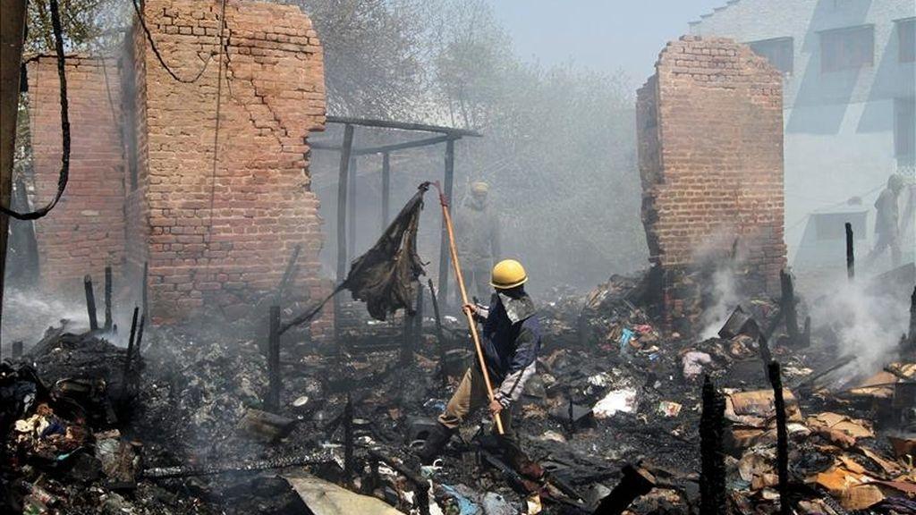 Un bombero remueve los escombros de un incendio en la Cachemira India, el pasado sábado 23 de abril de 2011. EFE/