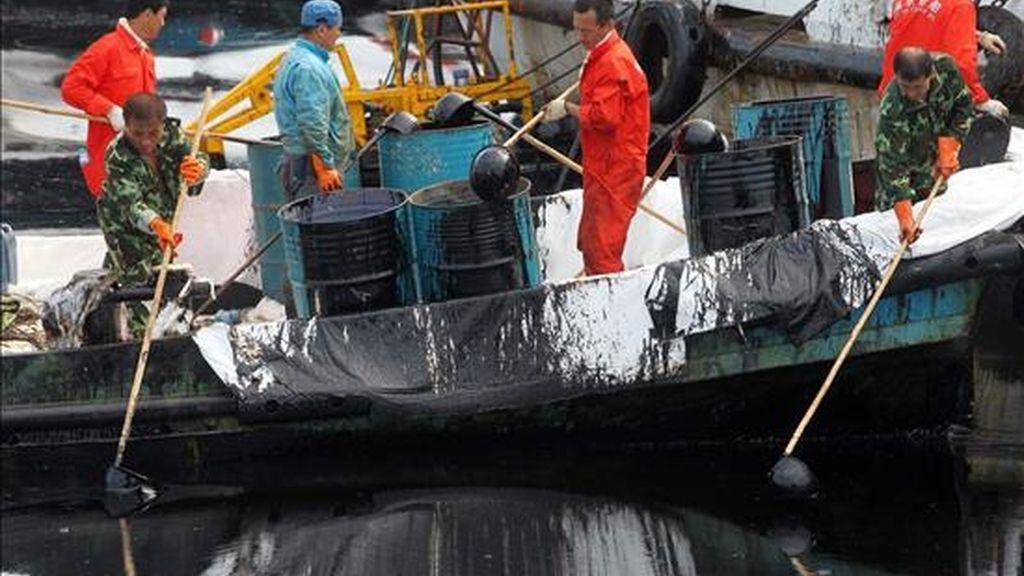 Vista de un grupo de trabajadores que recoge petróleo crudo que flota en el mar cerca a la población china de Dalian en la provincia de Liaoning el domingo 18 de julio de 2010. EFE