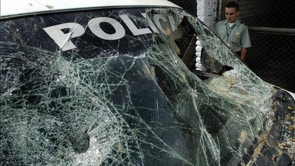 Un miembro de la policía colombiana observa, en Cali (Colombia), la camioneta donde se transportaban sus compañeros antes de ser emboscados en Buenos Aires, al suroeste del país. EFE