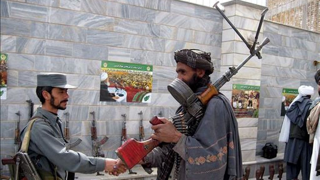 Un ex talibán afgano (d) saluda a un policía mientras él y otros militantes islámicos asisten a una ceremonia de rendición bajo el plan de amnistía del gobierno afgano respaldado por los Estados Unidos, el 10 de marzo pasado en Herat (Afganistán). EFE/Archivo