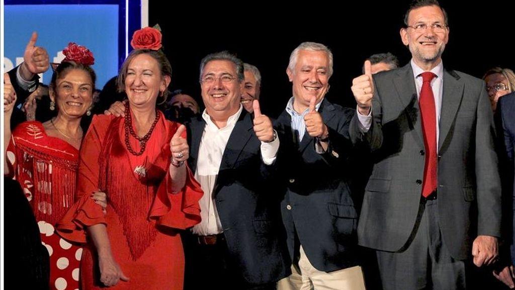 El presidente nacional del PP, Mariano Rajoy (c), junto al líder de los populares andaluces, Javier Arenas (i), y el candidato a la alcadia de Sevilla, Juan Ignacio Zoido, en la tradicional pegada de carteles que marca el inicio de la campaña para las elecciones Municipales y Autonómicas del 22 de mayo, esta noche en Sevilla. EFE