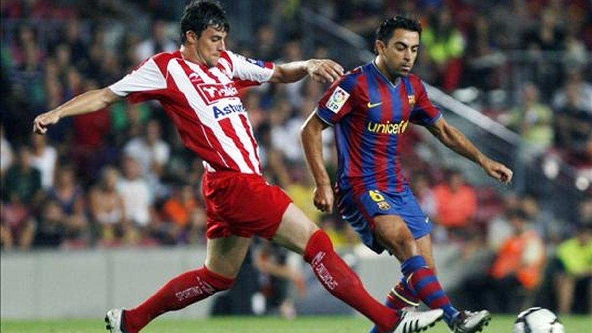 El centrocampista del FC Barcelona Xavi lucha un balón con el centrocampista del Sporting de Gijón, Cristián Portilla (i), durante el partido, correspondiente a la primera jornada de Liga de Primera División, disputado el año pasado en el Camp Nou. EFE/Archivo