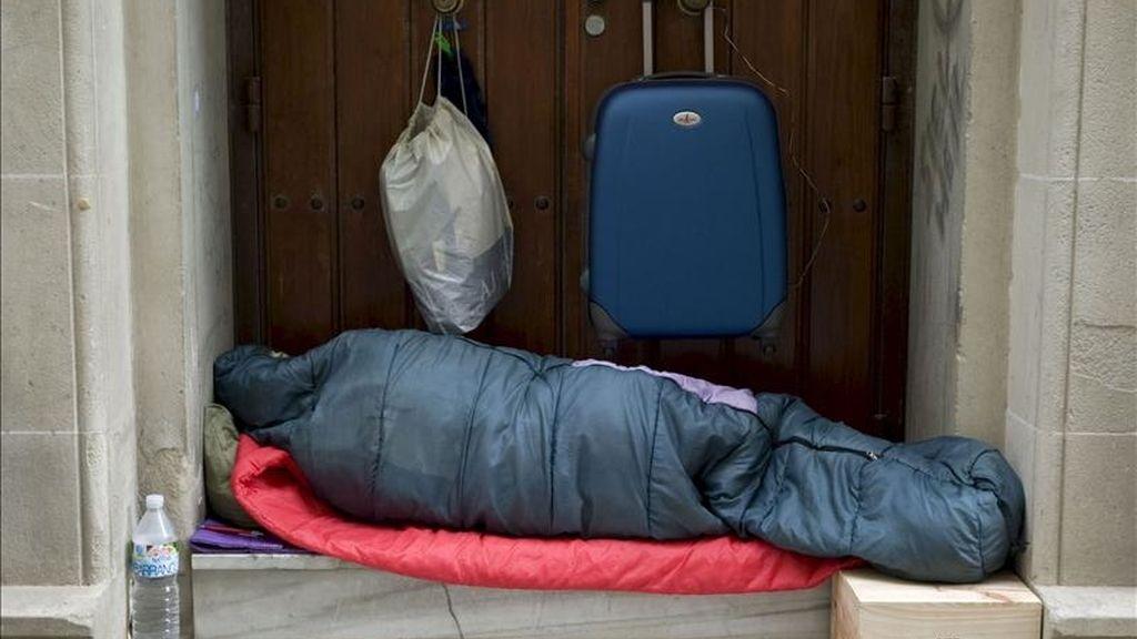 En la imagen, un indigente duerme en el portal de una vivienda. EFE/Archivo