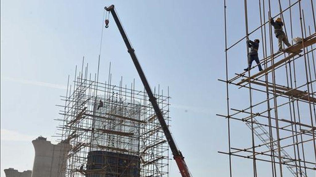 Trabajadores de la construcción edifican hoy un puente en Shenyang. La economía china creció en el primer trimestre del año un 6,1 por ciento, el dato trimestral más bajo desde que en 1992 el gobierno empezó a registrar este indicador, debido al impacto de la crisis, según datos presentados por el Buró Nacional de Estadísticas (BNE). EFE