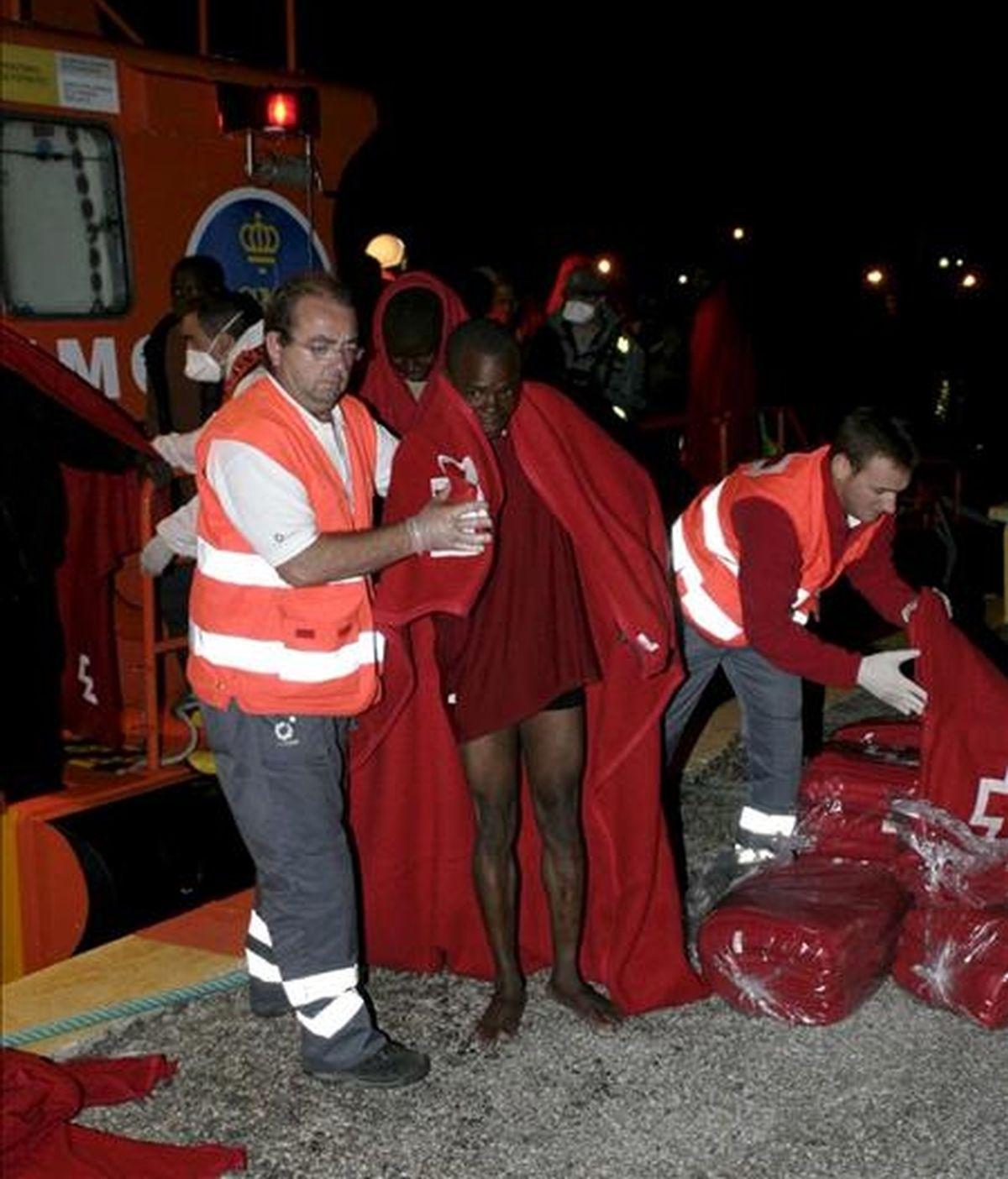 Un miembro de la Cruz Roja ayuda a uno de los 35 inmigrantes de origen subsahariano que viajaban en una patera a la deriva, a unas 30 millas de la costa granadina. EFE/Archivo