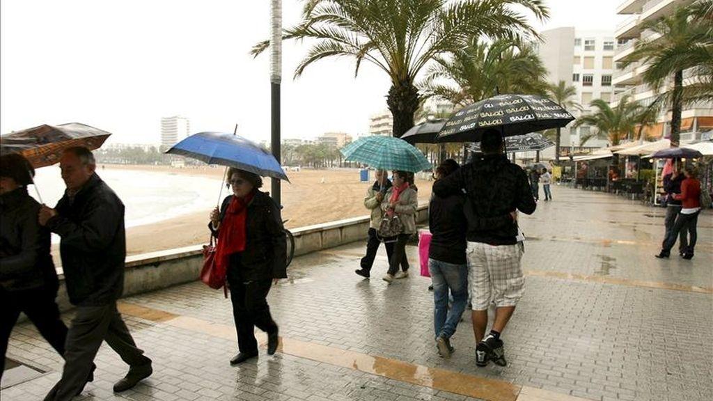 Varios turistas caminan por el paseo marítimo de la playa de levante de la localidad tarraconense de Salou. EFE/Archivo