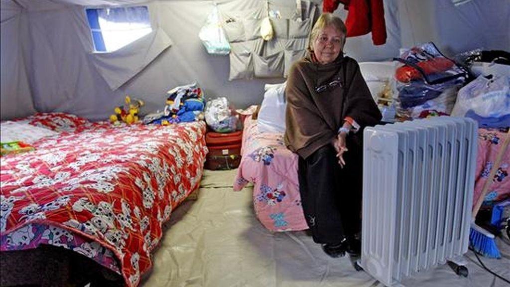 Una mujer trata de calentarse con un calentador eléctrico en su tienda del campamento para damnificados que se ubica en las cercanías de L'Aquila, Italia. EFE
