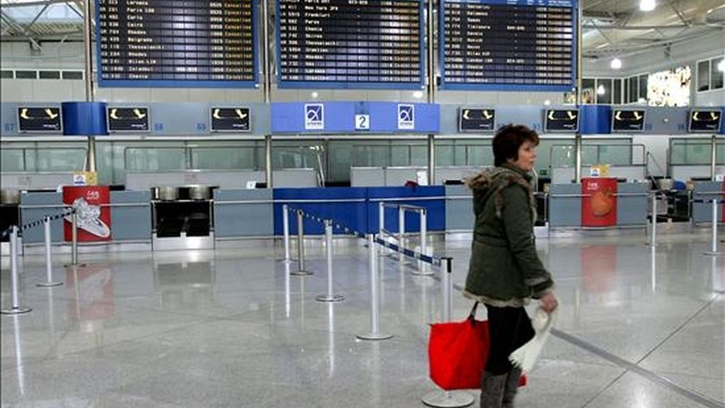 En la imagen, una mujer pasa ante los mostradores vacíos del aeropuerto de Atenas, Grecia.