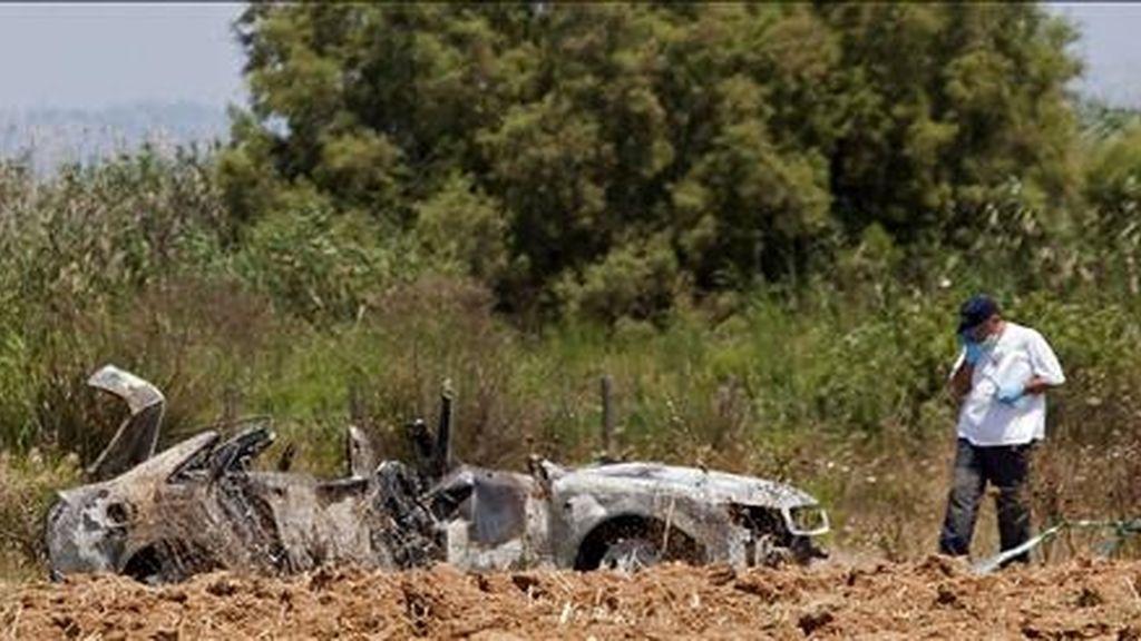 Agentes de la policía judicial de la Guardia Civil buscando pruebas en los alrededores del coche calcinado en cuyo maletero apareció el cadáver de una mujer, en la carretera de Muro a Can Picafort (Mallorca), el pasado martes. EFE
