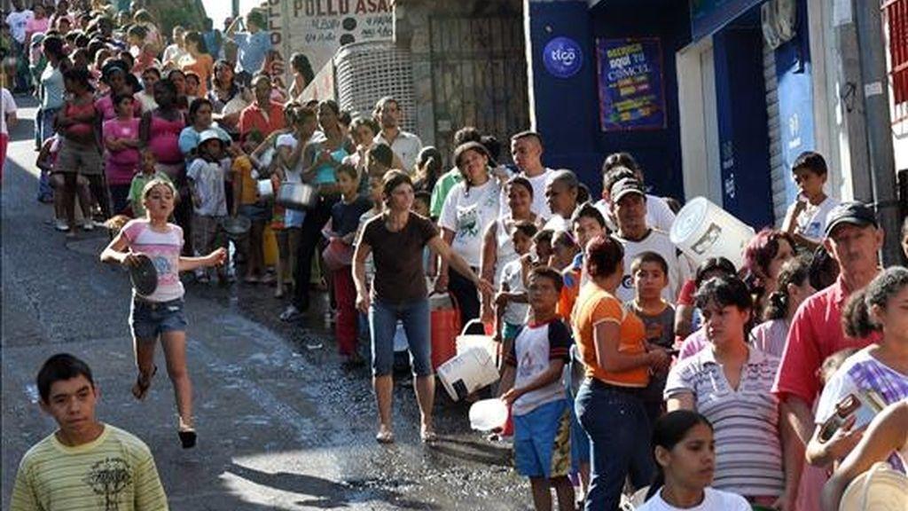 Varios habitantes del barrio Comuna 13 de Medellín (Colombia) hacen fila para recibir leche gratuita. Las personas de esta zona, en su mayoría desplazados por la violencia, carecen habitualmente de este suplemento alimenticio y sus hijos sufren de desnutrición. EFE/Archivo